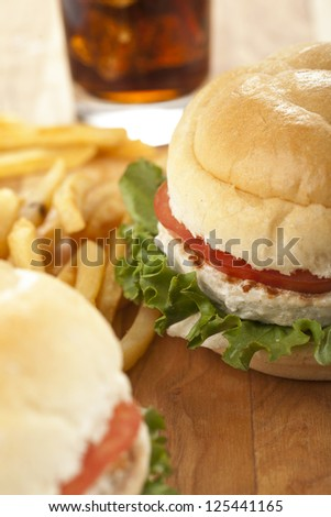 Cropped image of chicken sandwiches and potato fries with blurred soft drink on the background