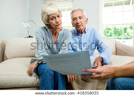 Cropped image of consultant showing report to aged couple at home - stock photo