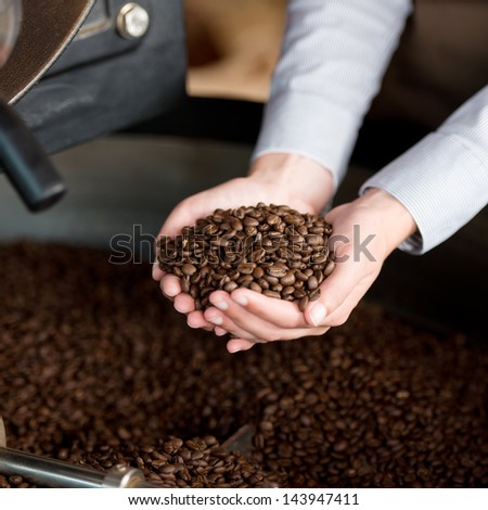 Cropped image of cooling container and waitress's hands holding coffee beans - stock photo