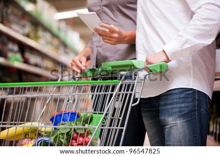 Cropped image of couple shopping groceries together with trolley at supermarket