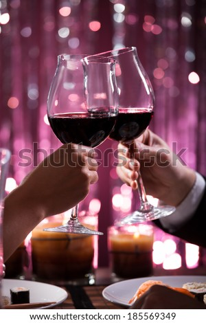 Cropped image of couple toasting wineglasses in restaurant