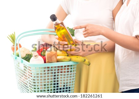 Cropped image of customers with full basket over white, a customer holding a bottle of oil while another pointing at it