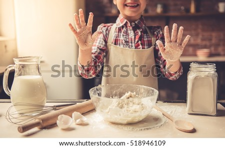 Cropped image of cute little girl in apron showing her palms and smiling while baking
