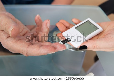 Cropped image of doctor checking glucose level in diabetic patient at clinic - stock photo