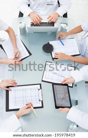 Cropped image of doctors examining medical reports at desk in clinic