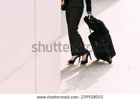 Cropped image of elegant business lady with luggage at the station - stock photo