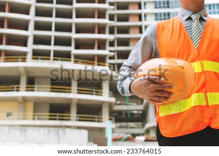 Cropped image of engineer with a hardhat at the construction site - stock photo