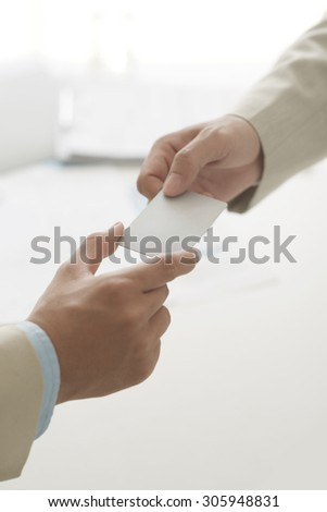 Cropped image of entrepreneur passing business card to his colleague - stock photo