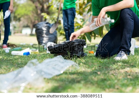 Cropped image of environmental activists collecting garbage - stock photo