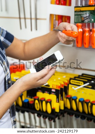 Cropped image of female customer holding cellphone and screwdriver in hardware store - stock photo