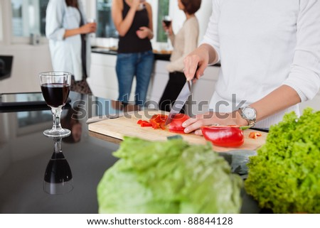 Cropped image of female cutting vegetables while friends having drink in background - stock photo