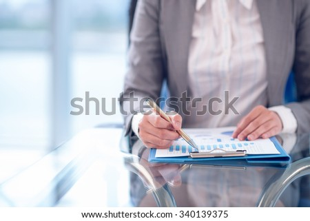 Cropped image of female entrepreneur analyzing financial report - stock photo