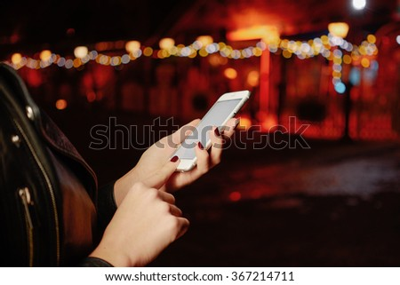 Cropped image of female hands using smart-phone with blank copy space screen on a bokeh background - stock photo