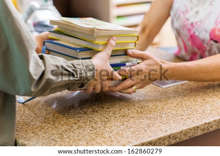 Cropped image of female librarian taking books from boy at checkout counter in library - stock photo