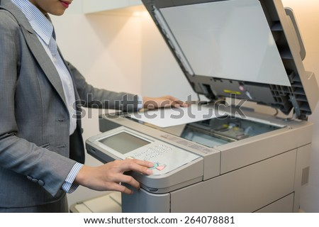 Cropped image of female manager using copier