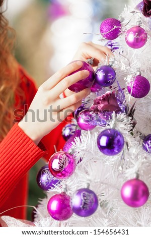 Cropped image of female owner hanging balls on Christmas tree at store - stock photo