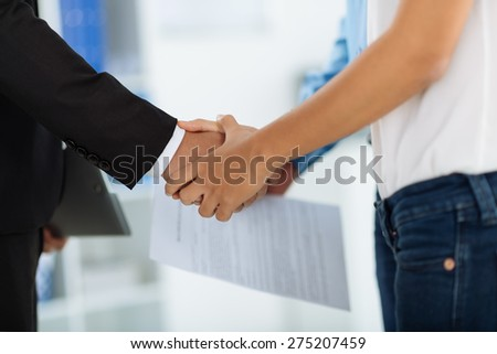 Cropped image of financial advisor and client shaking hands - stock photo