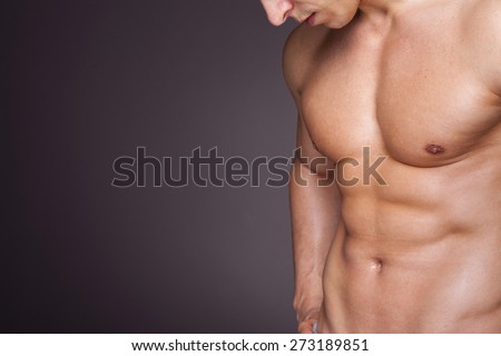Cropped image of fit man showing six pack abs - stock photo
