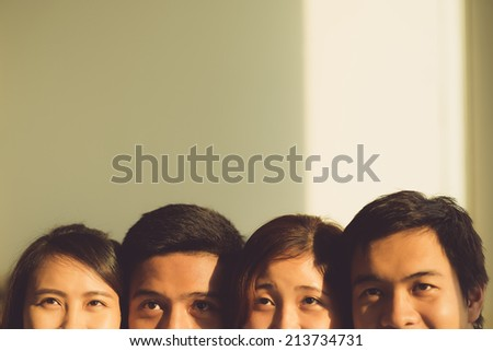 Cropped image of four young people looking up - stock photo