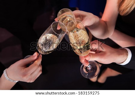 Cropped image of friends toasting champagne flutes at nightclub - stock photo