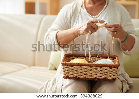 Cropped image of grandmother knitting at home - stock photo