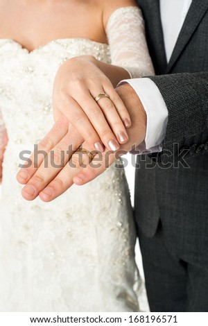 Cropped image of groom displaying their wedding rings