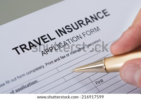 Cropped image of hand filling travel insurance form on desk