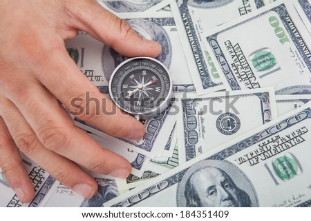 Cropped image of hand holding compass on US paper currency - stock photo