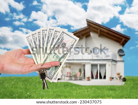 Cropped image of hand holding key and dollar notes against house - stock photo