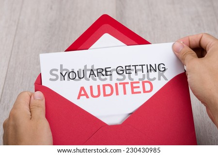 Cropped image of hand holding You Are Getting Audited card in envelope - stock photo