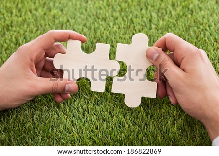 Cropped image of hands connecting two puzzle pieces on grass - stock photo