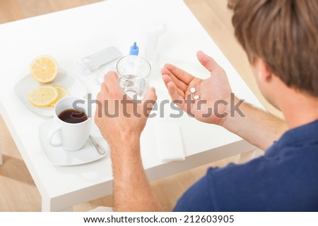 Cropped image of hands holding pills and water at home