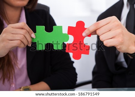 Cropped image of hands joining puzzle pieces