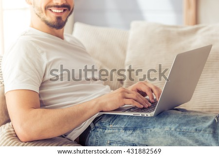 Cropped image of handsome man using a laptop, looking at camera and smiling while sitting on the sofa at home - stock photo
