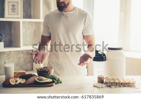 Cropped image of handsome young sportsman preparing sport nutrition in kitchen at home