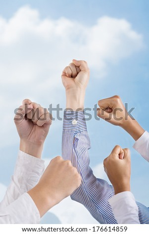 Cropped image of human fists in the air in the sign of power over the sky  - stock photo