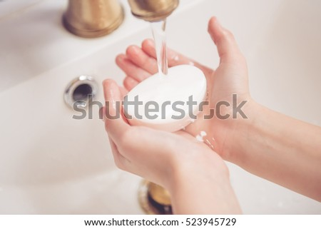Cropped image of  little boy washing hands with a soap in bathroom