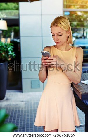 Cropped image of lovely young woman sending text message with mobile phone, charming hipster girl chatting on cell phone standing at coffee shop, female student connecting to wireless on telephone - stock photo