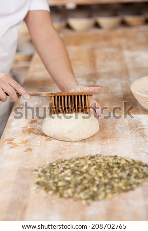 Cropped image of male chef applying butter on dough with brush at bakery kitchen counter - stock photo