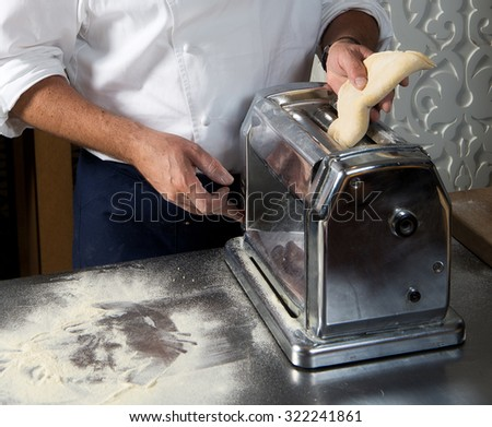 Cropped image of male chef processing  pasta sheet in machine at kitchen