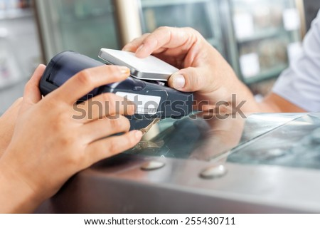 Cropped image of male customer making payment through smartphone in butchery - stock photo