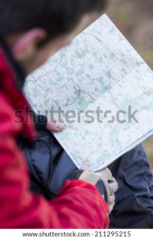 Cropped image of male hiker reading map - stock photo