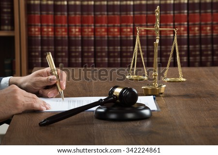 Cropped image of male judge writing on legal documents at desk in courtroom - stock photo