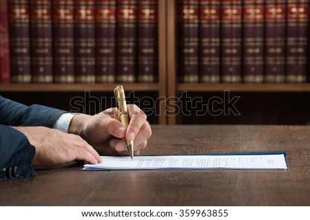 Cropped image of male lawyer writing on legal documents at desk in courtroom - stock photo