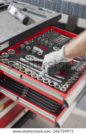 Cropped image of male mechanic taking tool from drawer in car workshop - stock photo