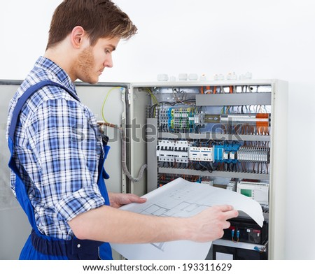 Cropped image of male technician analyzing blueprint in front of fusebox