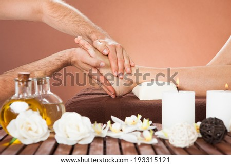 Cropped image of male therapist massaging female customer's foot at beauty spa - stock photo
