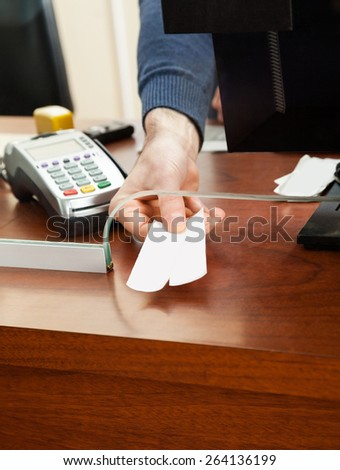 Cropped image of male worker holding tickets at box office counter - stock photo