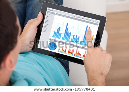 Cropped image of man analyzing graphs on digital tablet at home - stock photo
