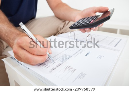 Cropped image of man calculating home finances at table - stock photo